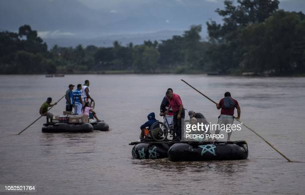 TOPSHOT Migrants heading to the US and residents use makeshift rafts to cross the Suchiate river natural border between Mexico and Guatemala in...