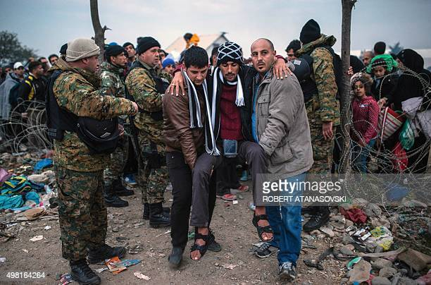 Migrants help a man as migrant and refugees walk past Macedonian policemen while crossing the GreekMacedonian border near Gevgelija on November 21...