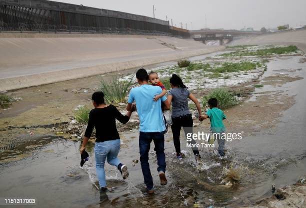 Migrants hold hands as they cross the border between the U.S. And Mexico at the Rio Grande river, on their way to enter El Paso, Texas, on May 20,...
