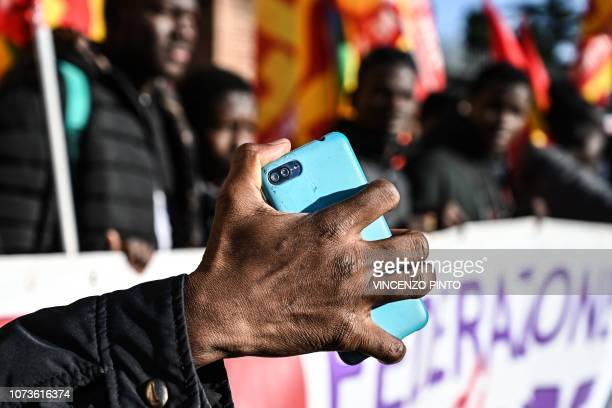 A migrants holds his mobile phone as people members of antiracism associations and migrants gather on Piazza della Repubblica in central Rome on...
