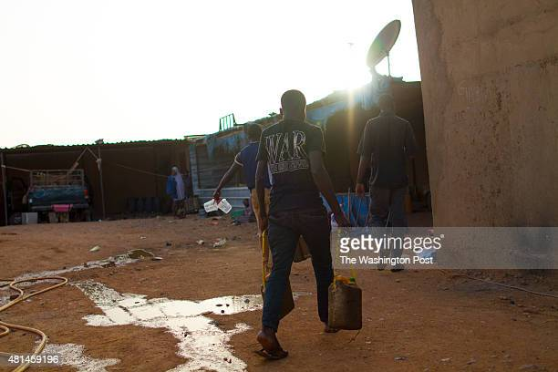 AGADEZ NIGER Migrants housed in what is commonly referred to as a 'ghetto' fill up their water containers as they prepare for night fall before...