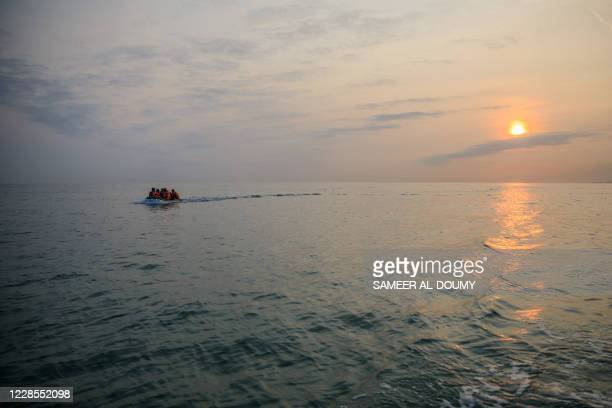Migrants in a dinghy wearing life jackets illegally cross the English Channel from France to Britain on September 11, 2020. - The number of migrants...