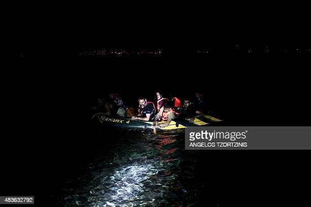 Migrants in an inflatable boat arrive on a beach on the Greek island of Kos, after crossing a part of the Aegean Sea between Turkey and Greece, on...