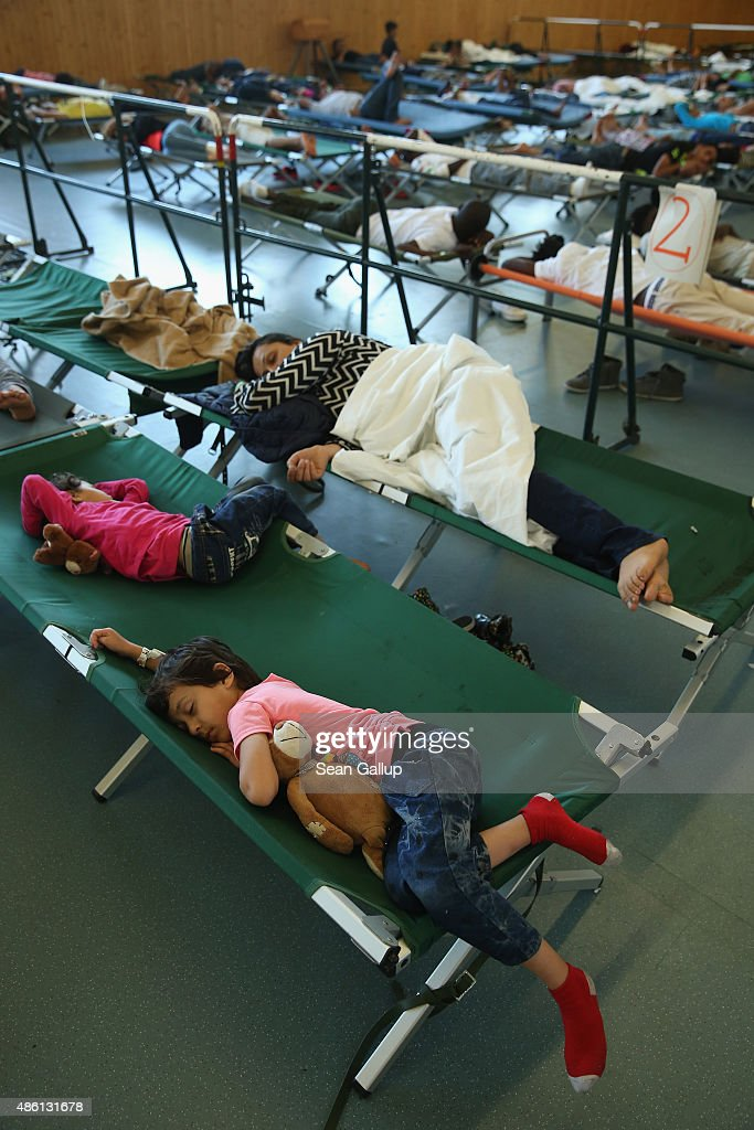 Migrants, including a mother and children from Afghanistan (foreground), who had arrived by train to Germany sleep on cots while waiting to register at a center for migrants at a facility of the German Federal Police (Bundespolizei) on August 31, 2015 in Rosenheim, Germany. German police monitor trains arriving from the Balkans and from Italy that go through Rosenheim and currently detain around 350 people a day for travelling without a passport. The police register the migrants, mostly from countries including Syria, Afghanistan and Eritrea, fingerprint them and check whether any are already in the European asylum-applicants or criminal databases. From there the migrants are free to travel within Germany to reception centers where they can apply for asylum. Up to 1,600 migrants are currently arriving in Bavaria in southern Germany a day and will seek asylum. Germany is expecting to receive 800,000 asylum-seeking migrants this year and is struggling to cope with the record number.