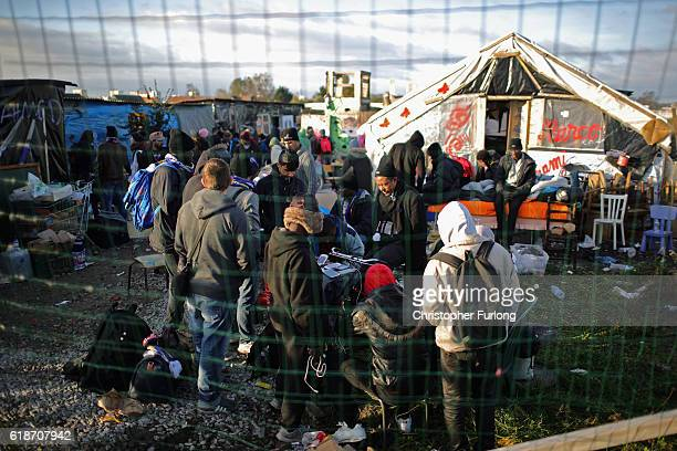 Migrants including minors wait outside the Calais Jungle school house after they were allowed by police back inside to shelter for the night on...