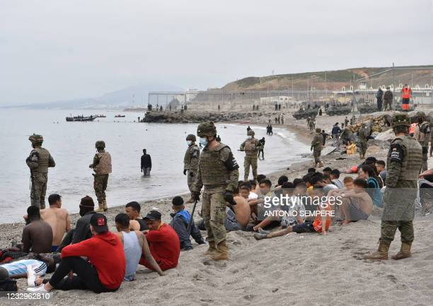 Migrants, including minors, who arrived swimming at the Spanish enclave of Ceuta, rest as Spanish soldiers stand guard on May 18, 2021 in Ceuta. -...