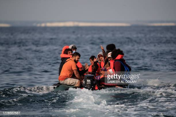 Migrants, including women and children, in a dinghy, react as they approach the southern British coastline as they illegally cross the English...