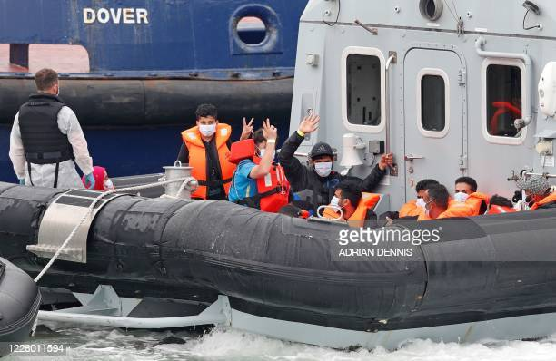 Migrants intercepted by UK Border Force officials whilst travelling in a RIB from France to Dover wave from the patrol vessel HMC Eagle as they are...