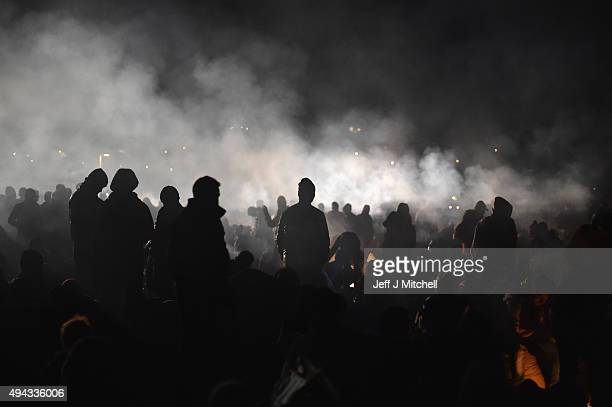 Migrants keep warm at a fire as they wait to be escorted by police to a holding camp in the village of Dobova on October 26, 2015 in Rigonce,...