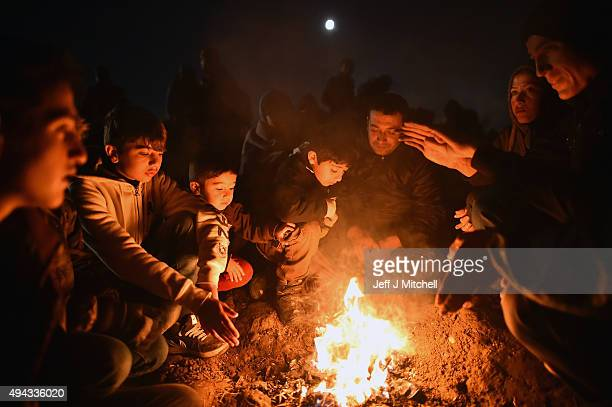 Migrants keep warm at a fire as they wait to be escorted by police to a holding camp in the village of Dobova on October 26 2015 in Rigonce Slovenia...