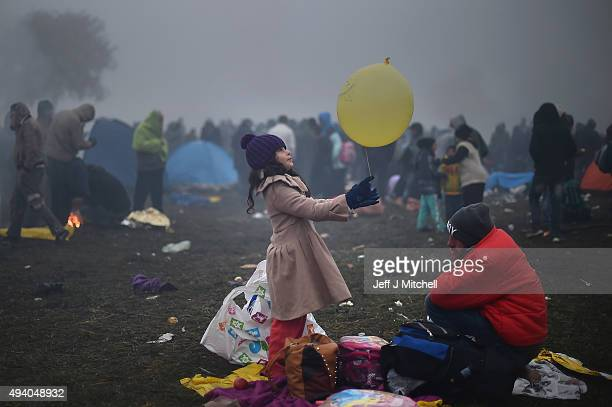 Migrants keep warm by fires as they are held back by the police near the village of Rigonce, before being walked to Brezice refugee camp on October...