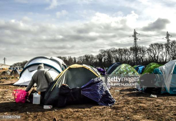TOPSHOT A migrants kneels outside a tent in a make shift camp in the vicinity of the former 'Jungle' camp site near the northern French port city of...