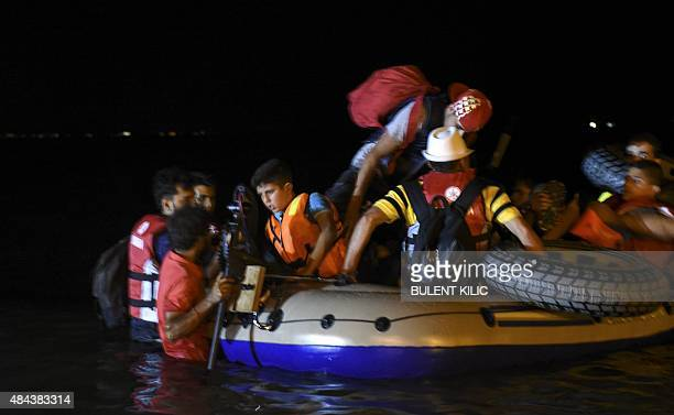 Migrants leave aboard a boat to the Greek island of Kos on early August 18 2015 off the shore of Bodrum southwest Turkey Authorities on the island of...