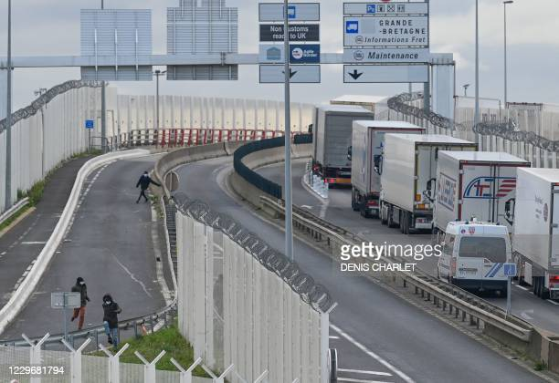 Migrants leave after attempting to climb into the back of lorries bound for Britain while traffic is stopped upon waiting to board shuttles at the...