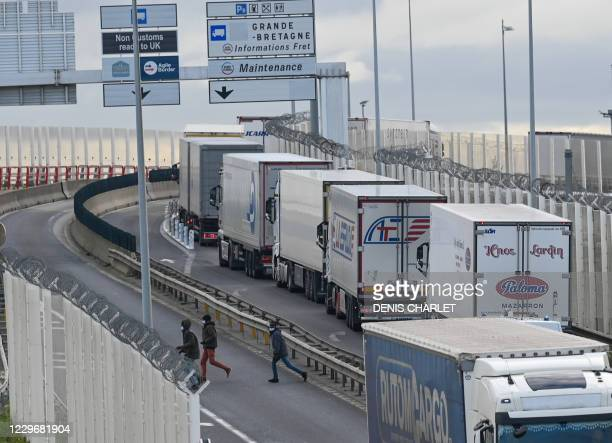 TOPSHOT Migrants leave after attempting to climb into the back of lorries bound for Britain while traffic is stopped upon waiting to board shuttles...