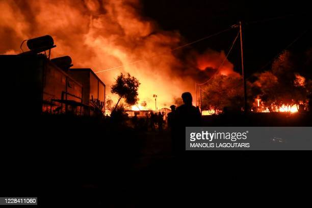 Migrants leave as a fire burns in the Moria camp on the island of Lesbos on September 9, 2020.
