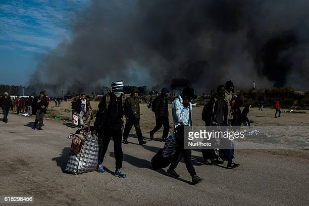 Migrants leave the burning Calais Jungle on October 26 2016 Huge fires destroyed a mayor part of the refugee camp today