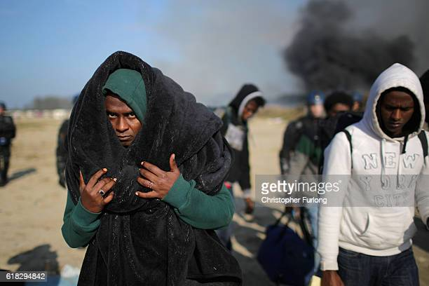 Migrants leave the Jungle camp as fires rage across the notorius camp believed to have been started by departing mirants as authorities demolish the...