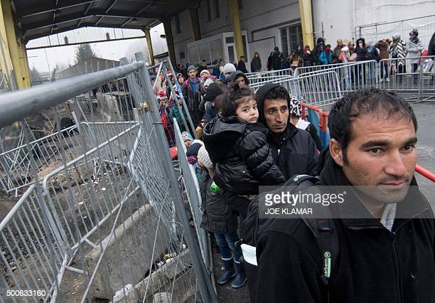 Migrants line up at a transit area between Austria and Slovenia at a border crossing in Spielfeld Austria on December 9 2015 Austria has begun to...