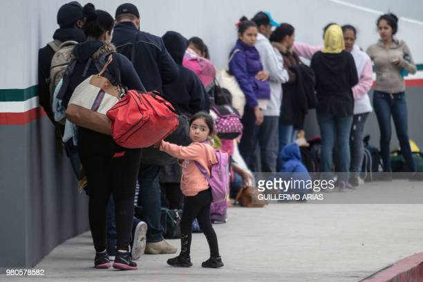 Migrants line up at El Chaparral port of entry in Tijuana Mexico in the boder with the United States on June 21 2018 US lawmakers were poised to vote...