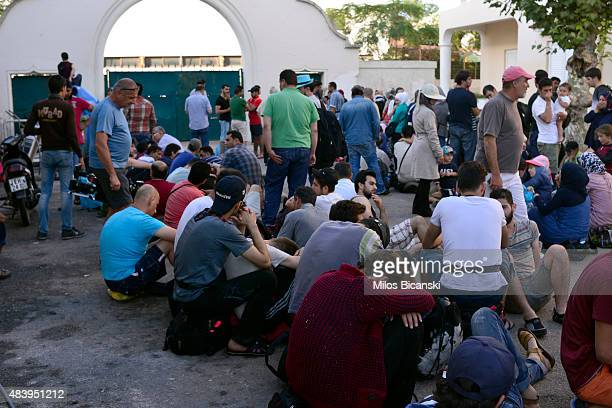 Migrants line up during a registration procedure at the national stadium on August 14 2015 in Kos Greece The Greek government is due to send a cruise...