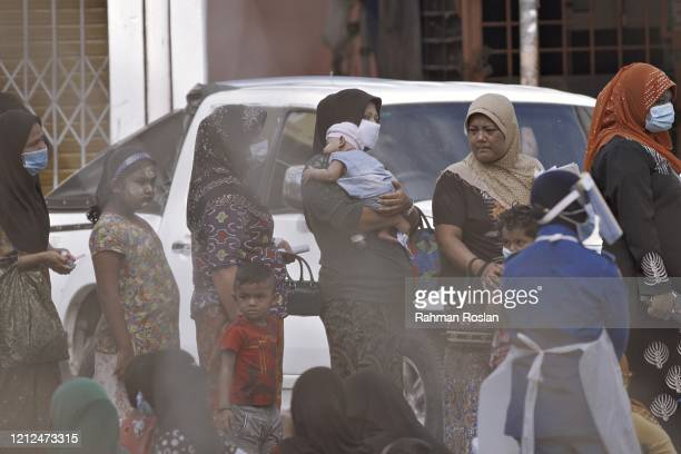 Migrants line up for document checks after being rounded up durng an immigration raid operation on May 11 2020 in Kuala Lumpur, Malaysia. Malaysian...