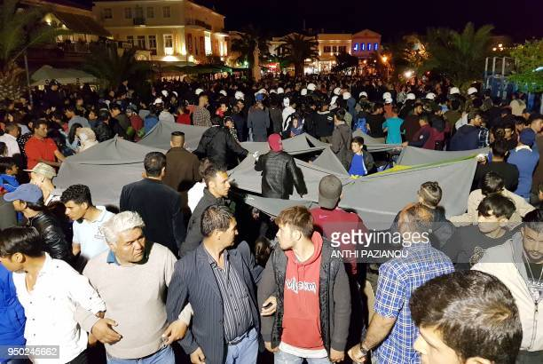 Migrants link their hands and hold blankets to protect their families as riot police try to keep away local protesters at the town of Mytilene on the...