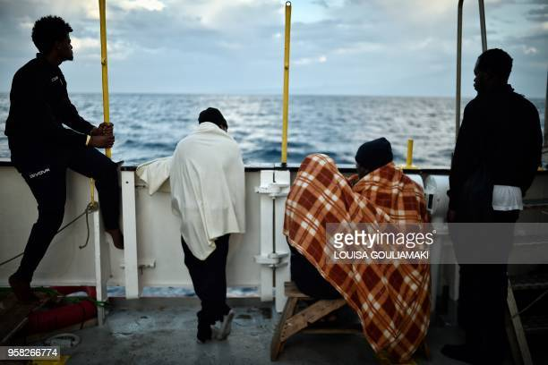 TOPSHOT Migrants look at the coastline as they stand aboard rescue ship MV Aquarius off the coast of Sicily on May 14 2018 Some 73 migrants of...