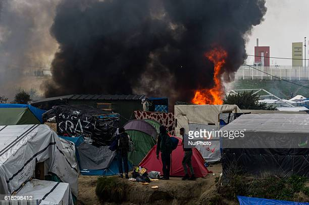 Migrants look in the Calais Jungle at a burning hut Huge fires destroyed a mayor part of the refugee camp today