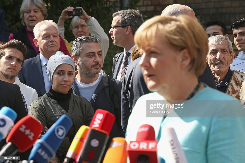 Migrants look on as German Chancellor Angela Merkel speaks to the media after she visited the AWO Refugium Askanierring shelter for migrants on September 10, 2015 in Berlin, Germany. Merkel visited several facilities for migrants today, including an application center for asylum-seekers, a school with welcome classes for migrant children and a migrant shelter. Thousands of migrants are currently arriving in Germany every day, most of them via the Balkans and Austria. Germany is expecting to receive 800,000 asylum applicants this year.
