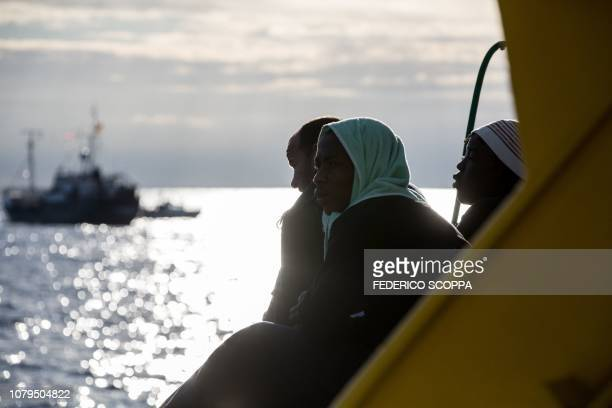 """Migrants look on from the deck aboard the Dutch-flagged rescue Vessel """"Sea Watch 3"""" sailing off Malta's coast on January 8, 2019. - Malta has reached..."""