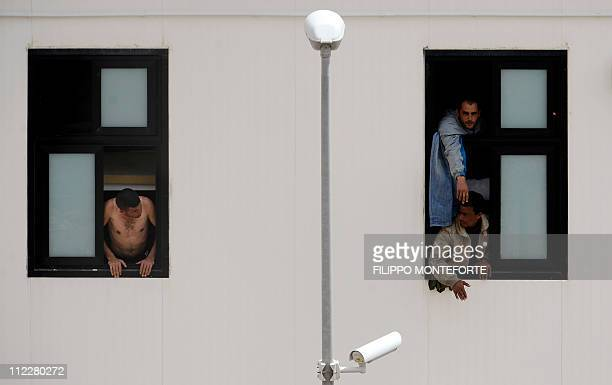 Migrants look out of their windows during a protest at a temporary detention center on the Italian island of Lampedusa on April 11 2011 Around 26000...