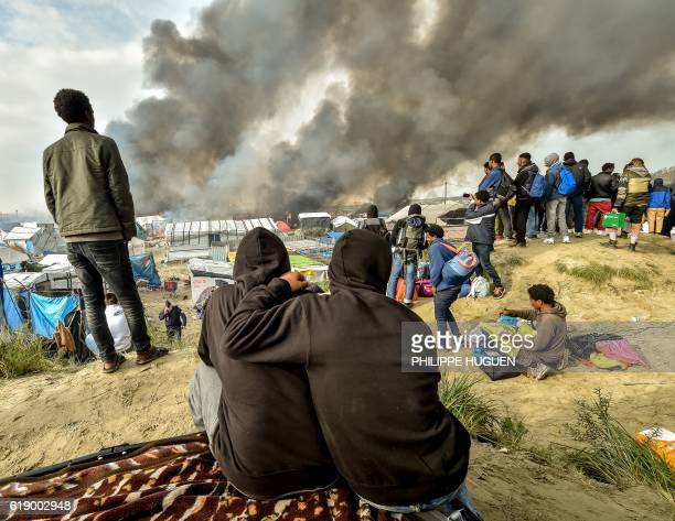 Migrants looks at the smoke rising from fires in the 'Jungle' migrant camp in Calais northern France on October 26 during a massive operation to...
