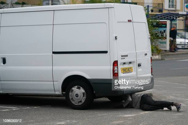 A migrants looks under a van for somewhere to hide at Ouistreham ferry port in the hope of reaching the UK as stowaways on vehicles on September 12...