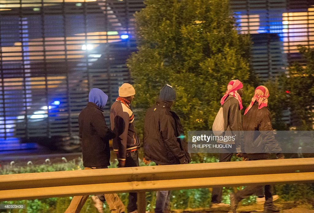 Migrants make their way towards the boarding docks on the Eurotunnel site in Coquelles near Calais, northern France, on late July 29, 2015. One man died Wednesday in a desperate attempt to reach England via the Channel Tunnel as overwhelmed authorities fought off hundreds of migrants, prompting France to beef up its police presence.