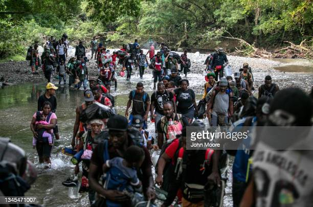 Migrants, most from Haiti, ford one of many rivers they will cross while on a trek through the infamous Darien Gap on their journey towards the...