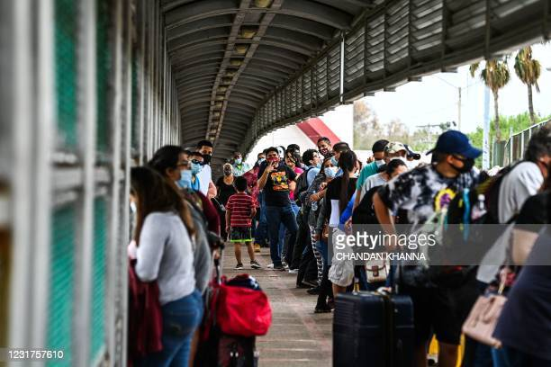 Migrants mostly form Central America wait in line to cross the border at the Gateway International Bridge into the US from Matamoros, Mexico to...