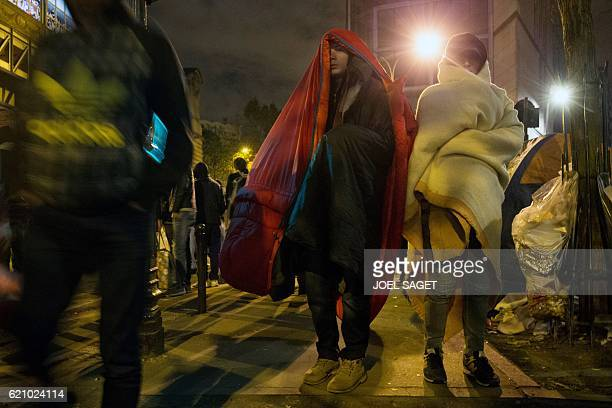 Migrants mostly from Afghanistan wrapped in blankets stand during an evacuation of a makeshift camp near Stalingrad metro station in Paris on...