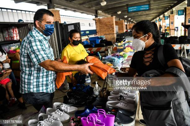Migrants mostly from Central America get essentials donated by an NGO Team Brownsville, as they wait for their Covid-19 tests after they are dropped...