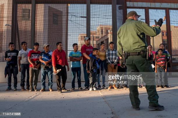 Migrants mostly from Central America que to board a van which will take them to a processing center on May 16 in El Paso Texas About 1100 migrants...