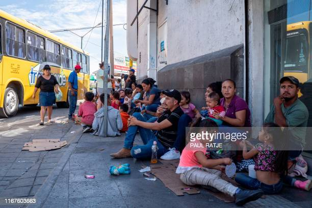 Migrants mostly from Mexico are pictured sitting on the ground waiting near the Paso del Norte Bridge at the MexicoUS border in Ciudad Juarez Mexico...
