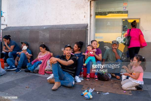 Migrants, mostly from Mexico, are pictured sitting on the ground waiting near the Paso del Norte Bridge at the Mexico-US border, in Ciudad Juarez,...