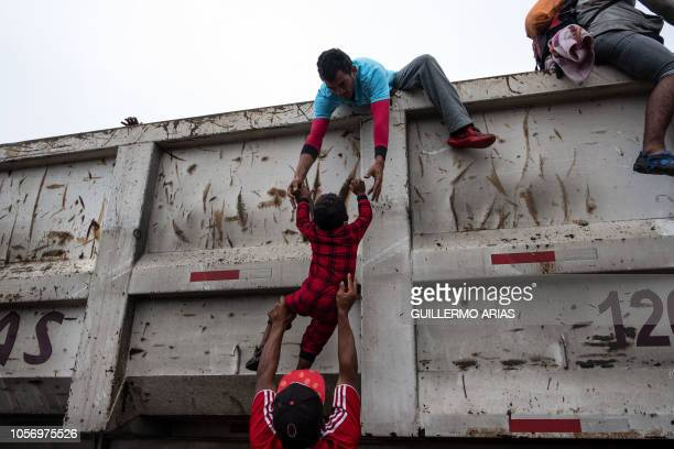 TOPSHOT Migrants mostly Hondurans heading in a caravan to the US help a child catch a ride on a truck on the road linking Sayula de Aleman and Isla...
