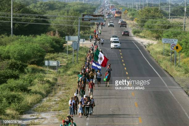 Migrants mostly Hondurans taking part in a caravan heading to the US hold Honduran and Mexican national flags as they walk along the road on their...