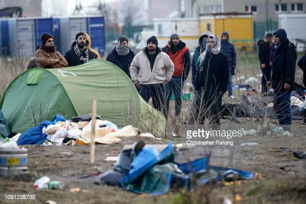 Migrants move their belongings as French police clear a migrant camp near Calais Port on January 08 2019 in Calais France In recent weeks there has...