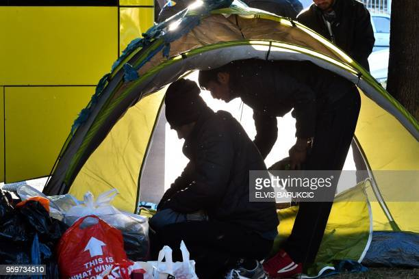 Migrants pack their belongings and their tents during the evacuation of a makeshift camp in a park across the City Hall in Sarajevo on May 18 in...