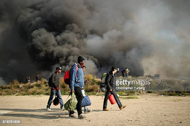 Migrants pack up and leave notorious Jungle camp as authorities demolish the site on October 26 2016 in Calais France Overnight fires broke out in...