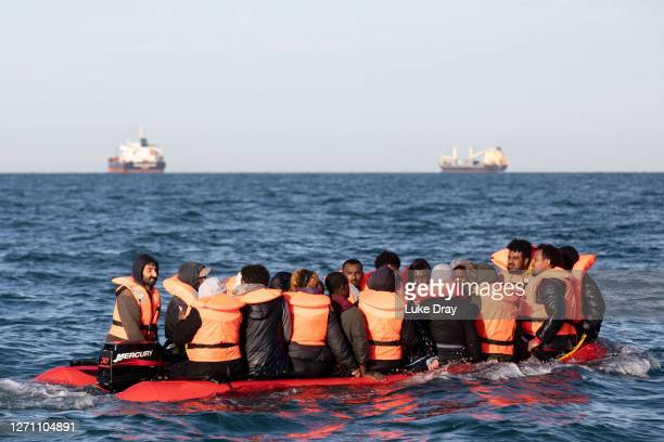 Migrants packed tightly onto a small inflatable boat attempt to cross the English Channel near the Dover Strait, the world's busiest shipping lane,...