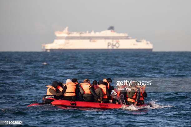Migrants packed tightly onto a small inflatable boat bail water out as they attempt to cross the English Channel near the Dover Strait, the world's...