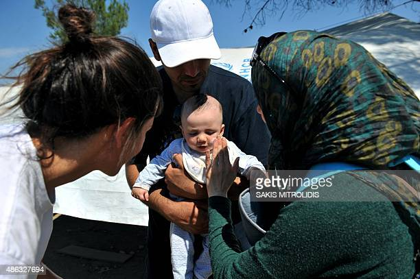 Migrants parents apply sunscreen cream on their baby as they wait to cross the Greek Macedonian border near the town of Idomeni northern Greece on...